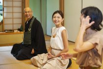 Zwei japanische Frauen und ein buddhistischer Priester knien im buddhistischen Tempel und reden. — Stockfoto