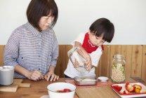 Femme et garçon japonais mûrs se tenant debout dans un magasin de ferme pour préparer la nourriture. — Photo de stock
