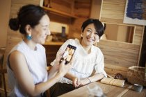 Two Japanese women sitting at a table in a vegetarian cafe, using mobile phone and taking photo. — Stock Photo