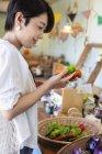 Japanese woman shopping fresh vegetables in a farm shop. — Stock Photo