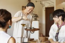 Donna giapponese che serve tè a clienti femminili in un caffè vegetariano . — Foto stock