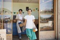 Duas mulheres japonesas sorridentes saindo da loja da fazenda . — Fotografia de Stock