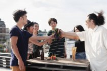Group of young Japanese men and women standing on rooftop in urban setting, toasting beer bottles. — Stock Photo