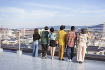 Group of men and women standing on rooftop in urban setting. — Stock Photo