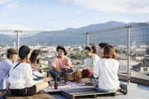Gruppo di giovani giapponesi seduti sul tetto in ambiente urbano, che bevono birra e suonano la batteria . — Foto stock