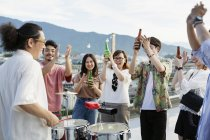 Smiling group of young Japanese men and women standing on rooftop in urban setting, drinking beer. — Stock Photo