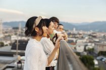 Group of young Japanese men and women standing on rooftop in urban setting. — Stock Photo