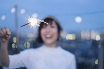Smiling young Japanese woman holding sparkler on roof in urban setting.. - foto de stock
