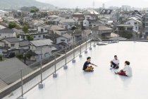 High angle view of young Japanese men sitting on rooftop in urban setting. — стокове фото