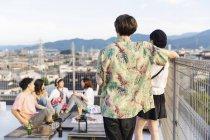 Groupe de jeunes Japonais hommes et femmes sur le toit en milieu urbain . — Photo de stock