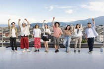 Smiling group of young Japanese men and women standing on rooftop in urban setting. — Stock Photo