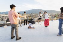Group of young Japanese men and women dancing on rooftop in urban setting. — Stock Photo