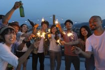 Group of young Japanese men and women with sparklers on rooftop in urban setting. — Stock Photo