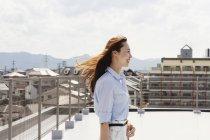 Sorridente donna giapponese in piedi sul tetto in ambiente urbano . — Foto stock