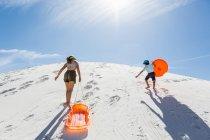 Enfants tirant des traîneaux et escaladant une dune de sable, monument national de White Sands, Nouveau-Brunswick — Photo de stock