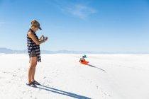 Mère photographiant son fils en traîneau sur des dunes de sable — Photo de stock