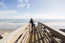 Adolescente menina na ponte de madeira pela praia, com sua bicicleta — Fotografia de Stock