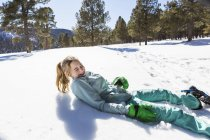 Teenage girl wearing snow shoes lying in the snow laughing — Stock Photo