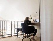 14 años de edad, chica mirando a la computadora portátil en su loft espacio - foto de stock