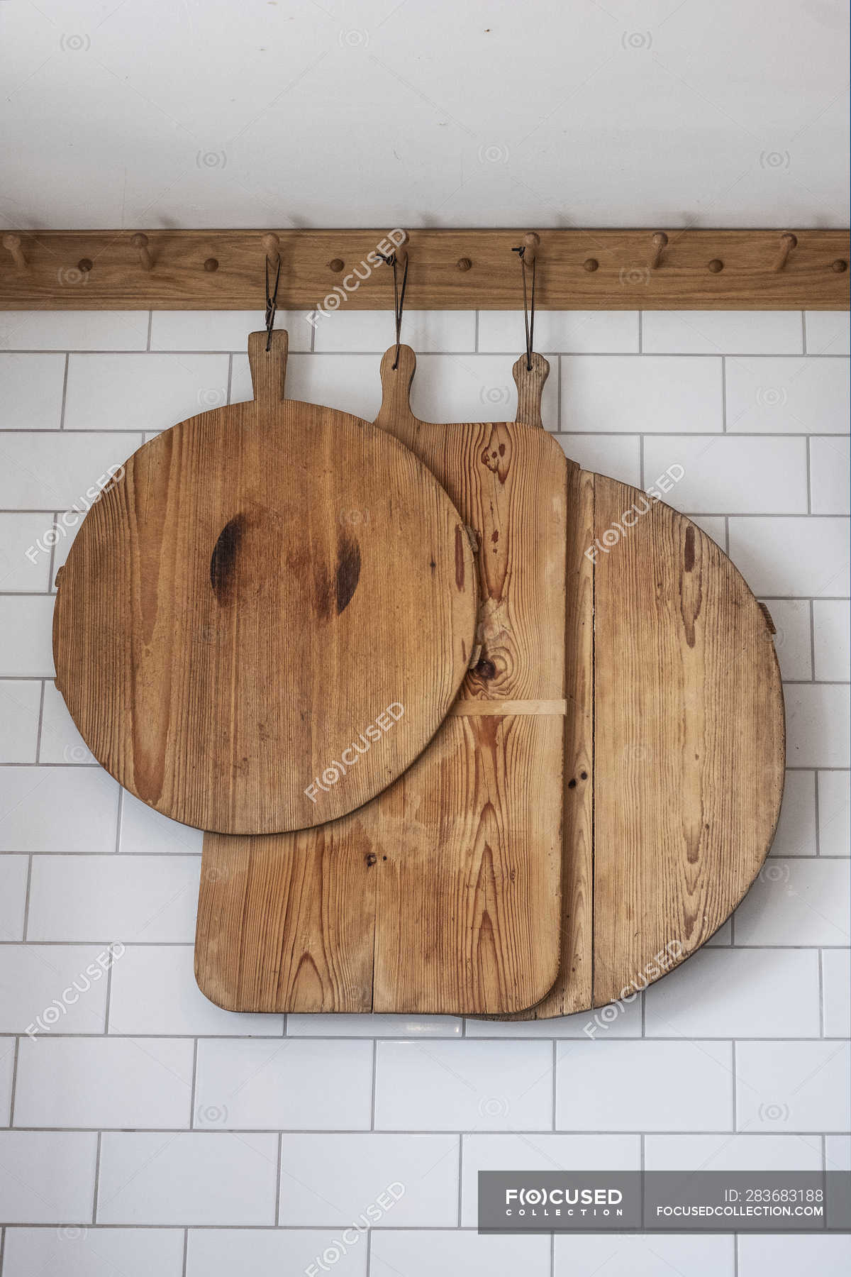 Small Selection Of Wooden Cutting Boards Hanging On Tiled White Wall Vertical Tiles Stock Photo 283683188