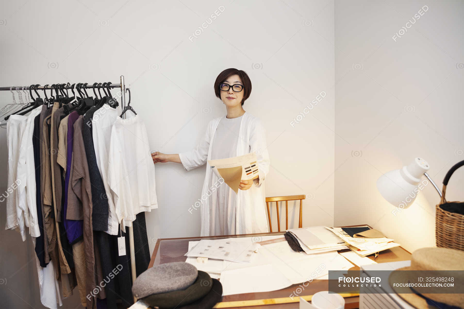 Japanese woman in glasses working at a desk in a small fashion boutique. —  female, textile - Stock Photo | #325498248