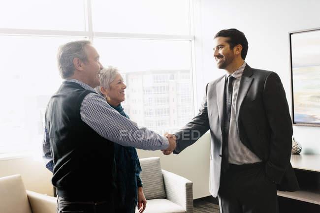 Mann Gruß ein älteres Paar in einem Büro — Stockfoto