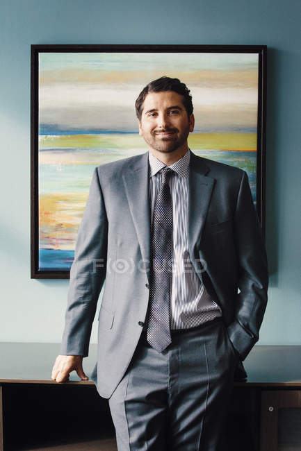 Man in a suit  in front of an artwork — Stock Photo