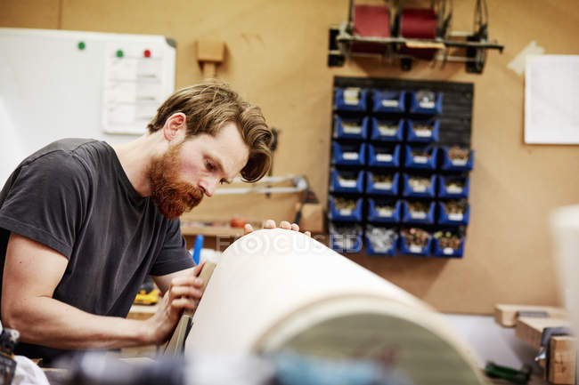 Man working on a curved wooden piece. — Stock Photo