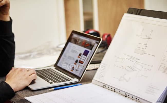 Человек, используя ноутбук на верстаке — стоковое фото