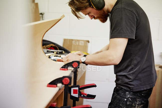 Человек на верстак, работающих на изогнутых деревяшкой — стоковое фото