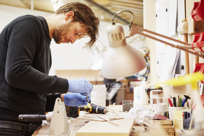 Man standing at a workbench. — Stock Photo