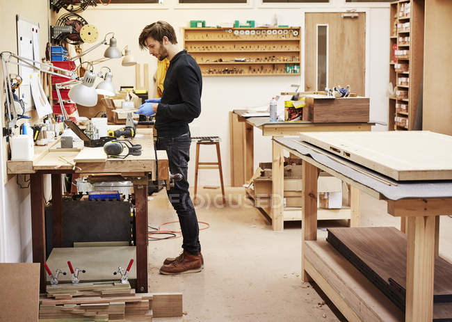Man standing at a workbench — Stock Photo
