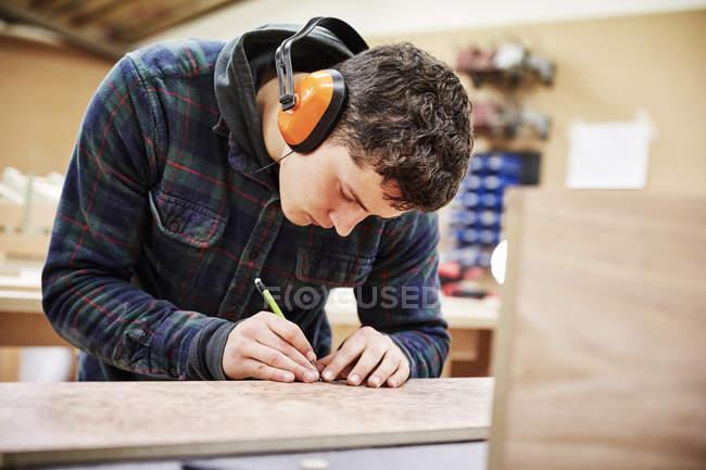 Homme marquant un morceau de bois — Photo de stock