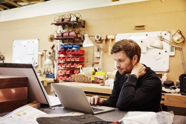 Людина, що сидить за допомогою портативного комп'ютера. — стокове фото