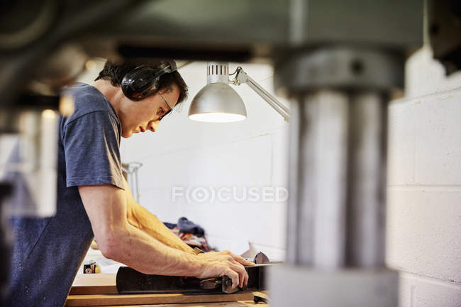 Man in ear defenders holding wood — Stock Photo