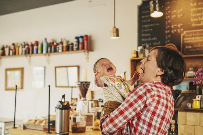 Frau hält ein weinendes baby — Stockfoto