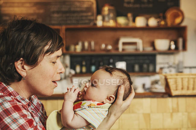 Woman holding her baby daughter's head — Stock Photo
