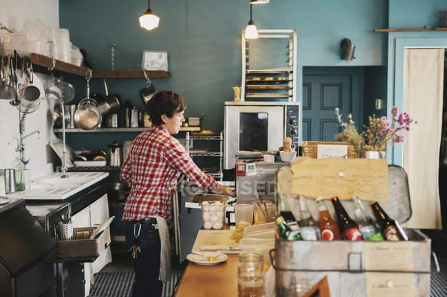 Donna che lavora dietro il bancone — Foto stock