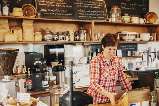 Женщина в клетчатой рубашке, работая за счетчик — стоковое фото