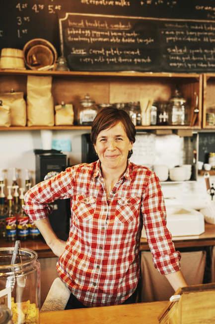 Frau im karierten Hemd hinter dem Tresen arbeiten — Stockfoto