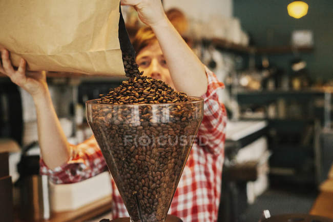 Woman pouring coffee beans into a grinder hopper — Stock Photo
