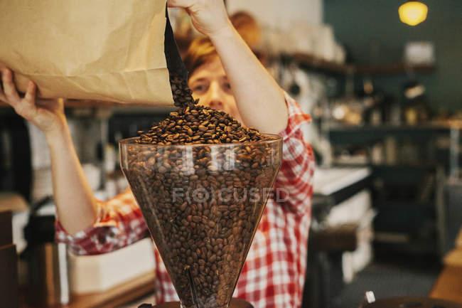 Mujer vertiendo granos de café en una tolva amoladora - foto de stock