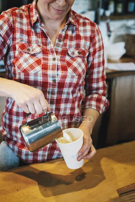 Женщина, работающая в маленькой кухне коммерческий — стоковое фото