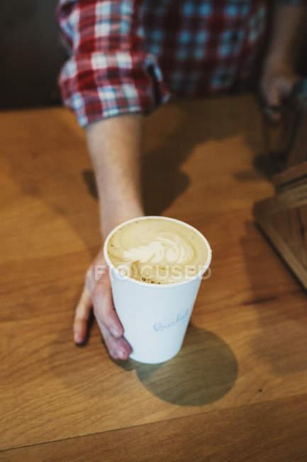 Personne mettre une tasse de café fraîchement préparé — Photo de stock