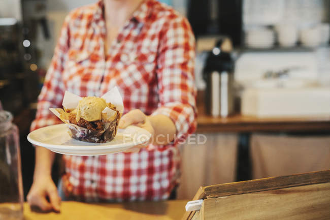 Woman in a coffee shop holding out a plate — Stock Photo