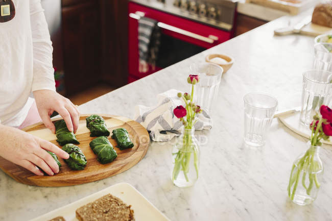 Жінка готує фаршировані листя винограду — стокове фото