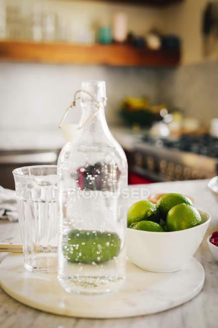 Бутылка воды и свежие нарезанные лимоны — стоковое фото