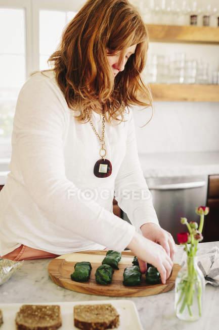 Frau bereitet gefüllte Weinblätter — Stockfoto