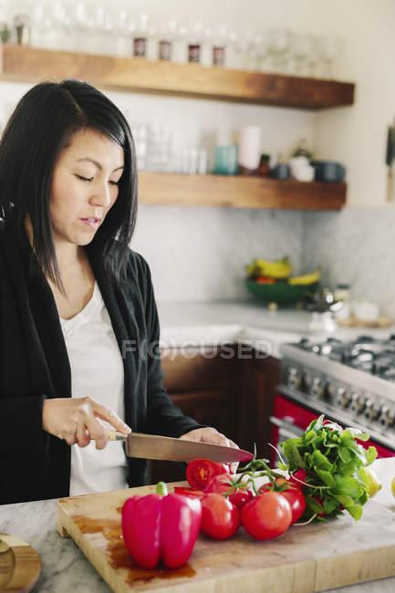 Femme en une cuisine préparer une salade — Photo de stock