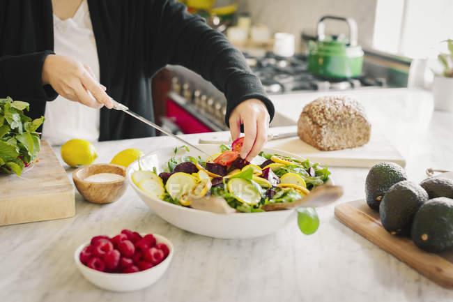 Frau bereitet in der Küche einen Salat zu — Stockfoto